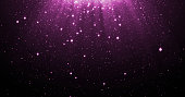 Abstract purple glitter particles background with shining stars falling down and light flare or glare overlay effect above for luxury premium product design template backdrop. Magic light radiance