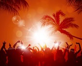party crowd raving among palms before sunset