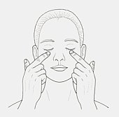 Black and white illustration of woman massaging skin under her eyes with her fingers