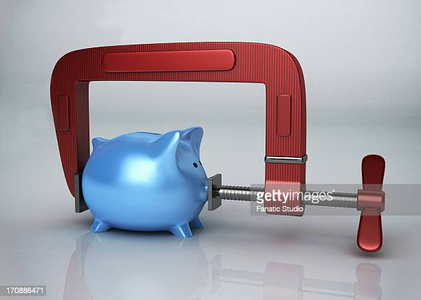 Blue piggy bank in clamp over colored background representing growth of money