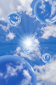Bubbles floating amongst clouds in blue sky