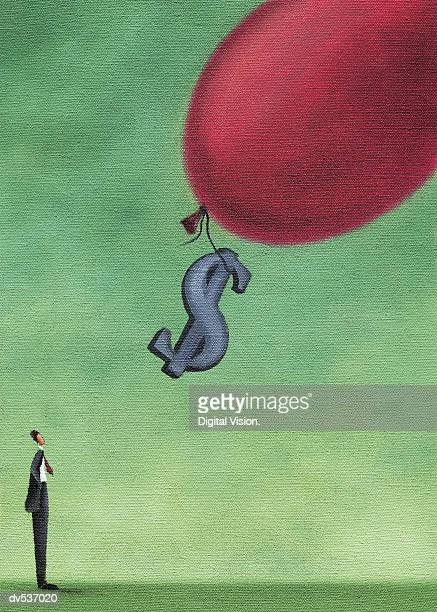 Businessman looking up at a dollar sign