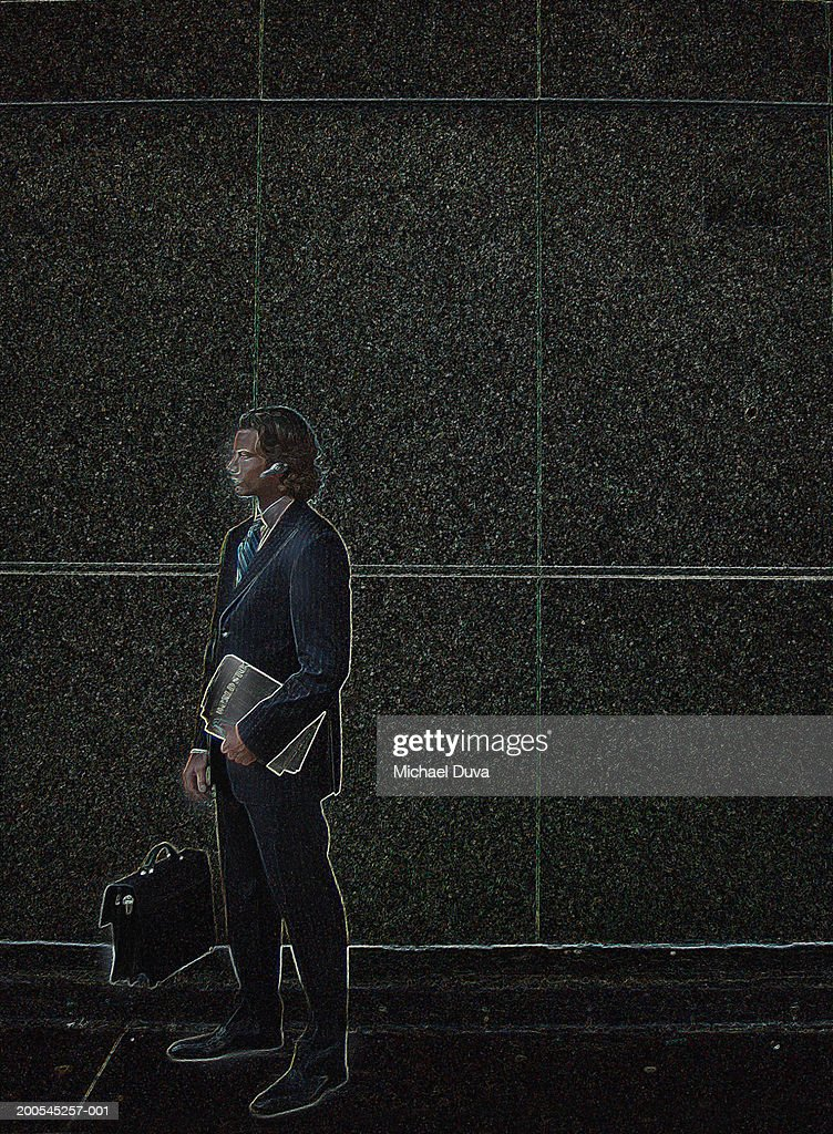 Businessman standing against wall holding file, side view : Stock Illustration