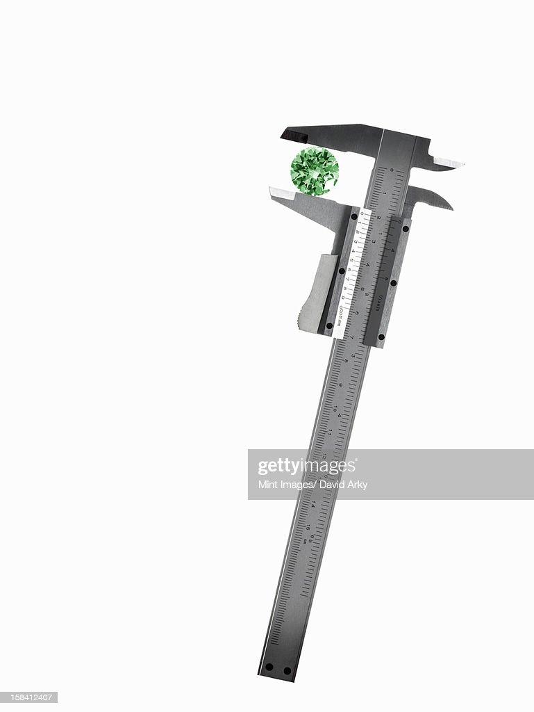 A caliper or guage measuring a green cyrstal cut gemstone. : Stock Illustration