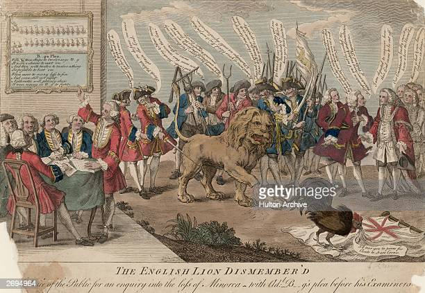 A cartoon showing a crowd of men discussing how to dissect a lion which has already lost a paw which is labelled 'Minorca' To the side a group of men...