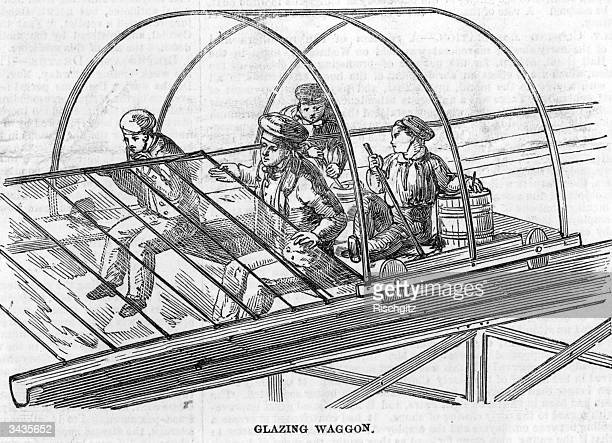 Two glaziers positioning panes of glass onto the iron framework of the Crystal Palace in London's Hyde Park while their young assistants mix putty at...