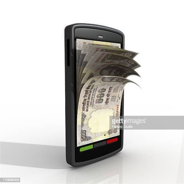 Conceptual shot of paper currency in cell phone depicting mobile banking
