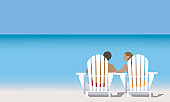 Couple on deck chair at beach, rear view