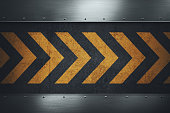 Black dirty grungy asphalt surface with yellow warning stripes. Polished metal plates with rivets. Place for your text.