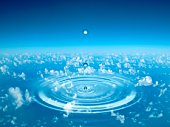 Drop of water falling onto water surface creating concentric circles, above a sea of clouds