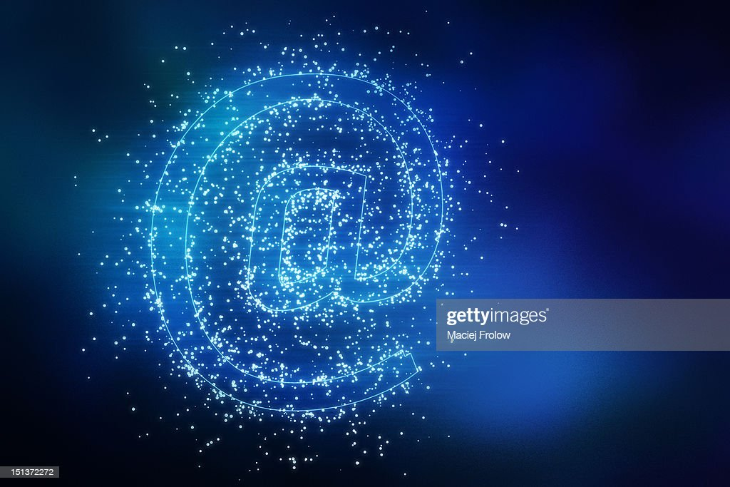Glowing 'at' symbol with light particles around : Stock Illustration