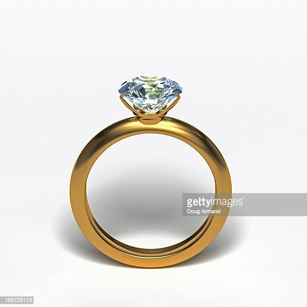 Gold diamond ring upright on white surface