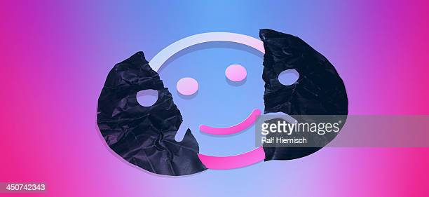 Graphic of a smiley face behind a torn sad face