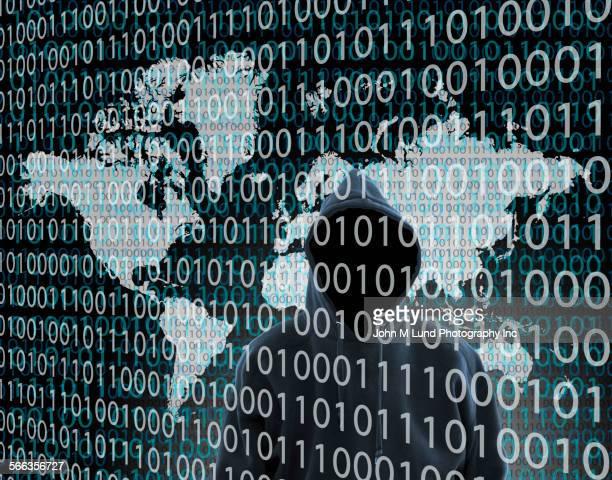 Hacker wearing hoody standing behind binary code