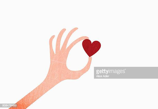 A hand holding heart shape against white background