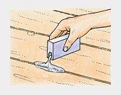 Hand pouring talcum powder into cracks between old floorboards to prevent squeaks