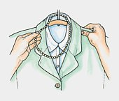 Hands placing necklace of beads over hanger holding jacket and blouse