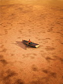 Male figurine in a boat on a dry land