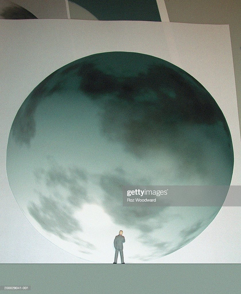 Man standing by giant globe, rear view : Stock Illustration