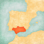 Andalusia on the map of Iberian Peninsula in soft grunge and vintage style on old paper.