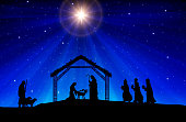Nativity scene with figures in black silhouette against blue starry sky with comet star lightbeam.