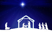 Nativity scene with figures in white silhouette against blue starry sky with comet star.