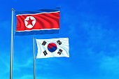 North and South Korea flags on the blue sky background. 3D illustration