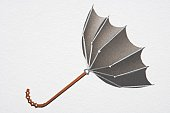 Open umbrella blown upwards from convex into concave shape by strong wind, side view.