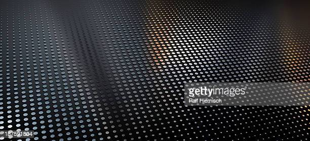 A pattern of metallic dots on a black background