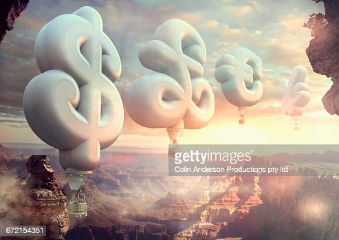 People floating in currency symbol hot air balloons at sunset