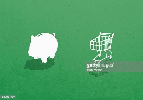 Piggy bank and shopping cart against green background