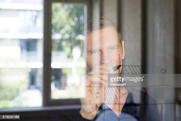 Portrait of business man drawing sketch on glass pane