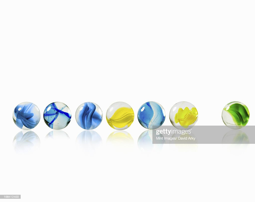 A row of glass marbles of different patterns and colours, with one separated from the rest. : Stock Illustration