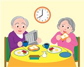 Senior man and woman talking and having breakfast, front view