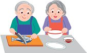 Senior man cooking fish and senior woman holding bowl, front view