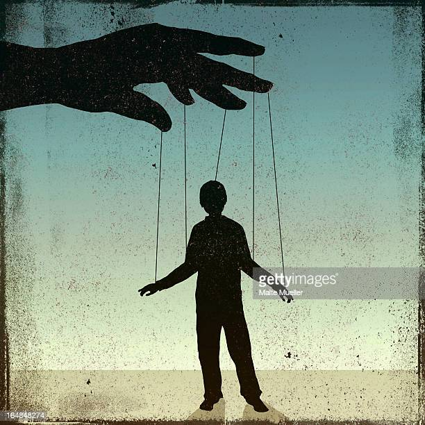 A silhouetted man being controlled by a puppeteer
