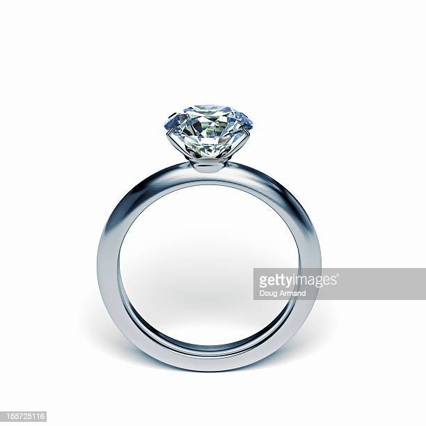 Silver diamond ring upright on white surface