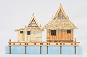 Thailand, Central Plains, wooden river houses with thatched roofs anchored to posts above the water line, front view.