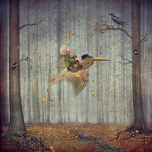 The little boy and brown pelican fly  in the autumn forest.