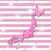 The shape of Japan made from pink sequins with a striped background