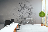 Side view of creative modern office with equipment, traveling sketch on concrete wall, bike, city view and decorative plant. Travel agency concept. 3D Rendering