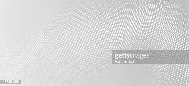 A wave pattern of white dots on a gray background