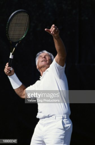 MATURE MAN WITH TENNIS RACKET : Bildbanksbilder
