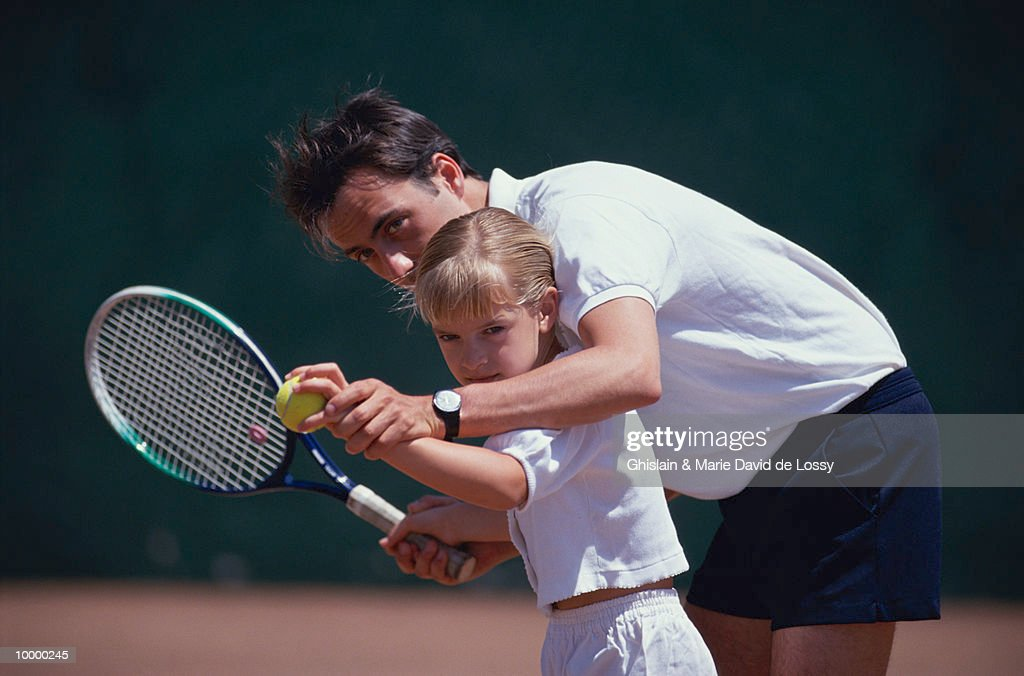 MAN TEACHING YOUNG GIRL TO PLAY TENNIS : Stock Photo