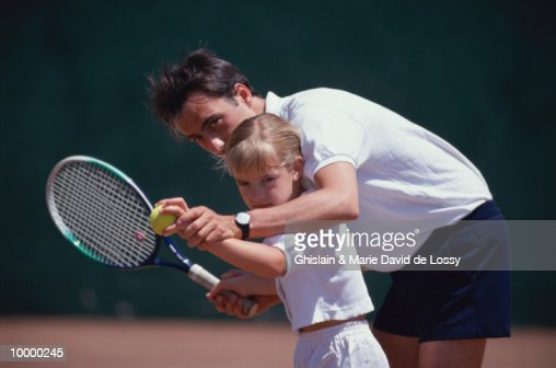 MAN TEACHING YOUNG GIRL TO PLAY TENNIS : Bildbanksbilder