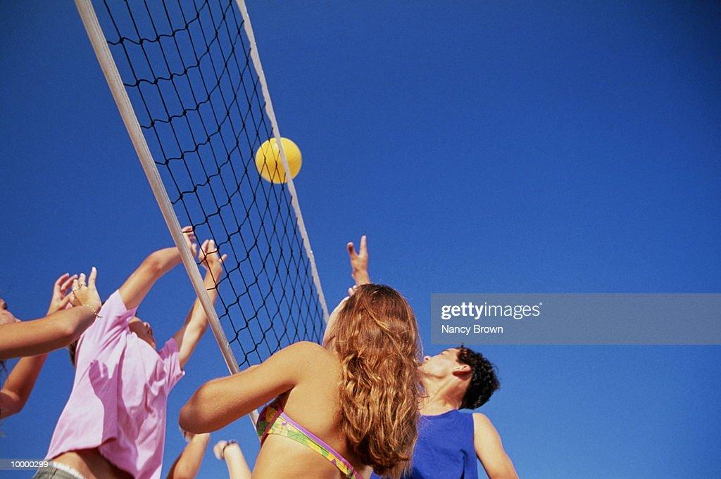 TEENS PLAYING VOLLEYBALL : Bildbanksbilder