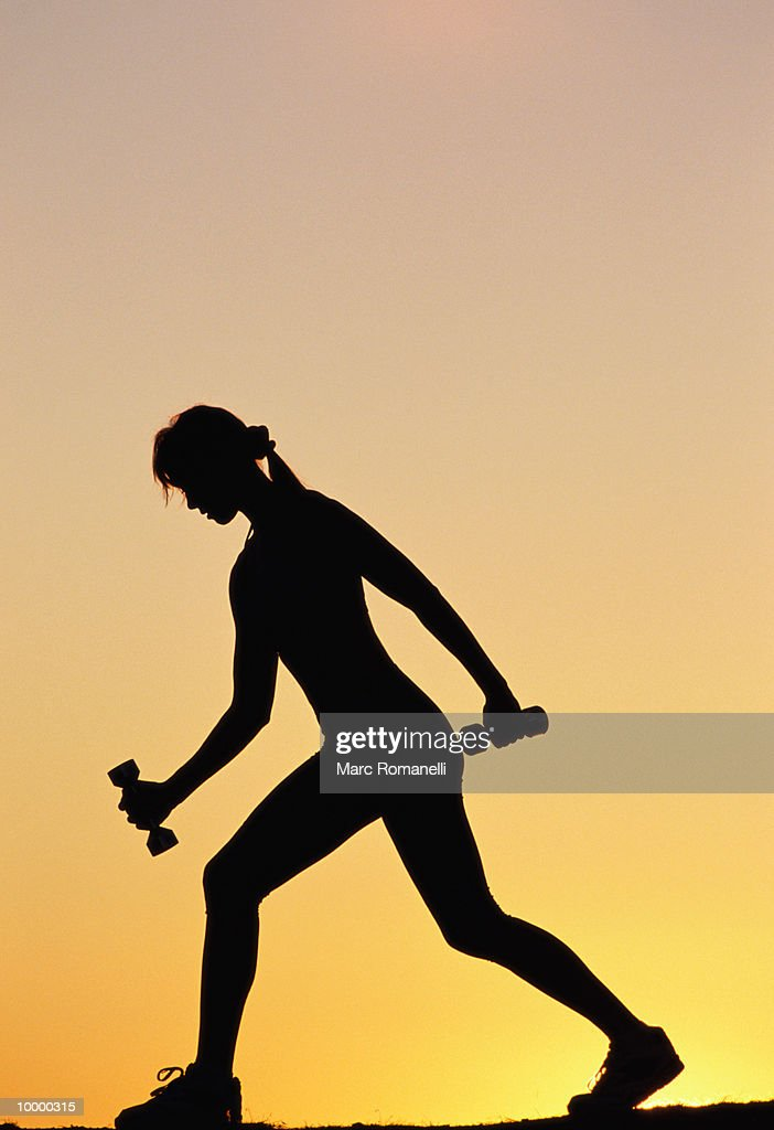 SILHOUETTE OF A WOMAN WITH DUMBBELLS : Stockfoto