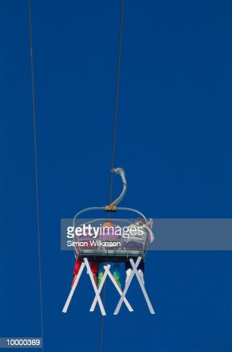 BACKVIEW OF THREE SKIERS ON CHAIR LIFT : Foto stock