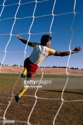 SOCCER PLAYER VIEWED THRU NET : ストックフォト