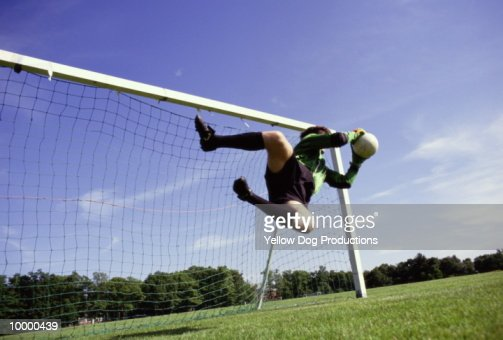 GOALIE IN MIDAIR WITH SOCCER BALL : Stock Photo